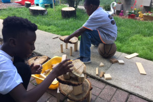 two young kids creating a wood art