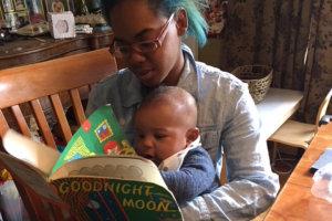 teacher reading a book to a cute toddler